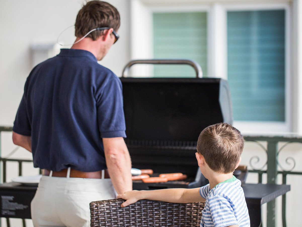 Man and boy grilling a family friendly meal of hot dogs